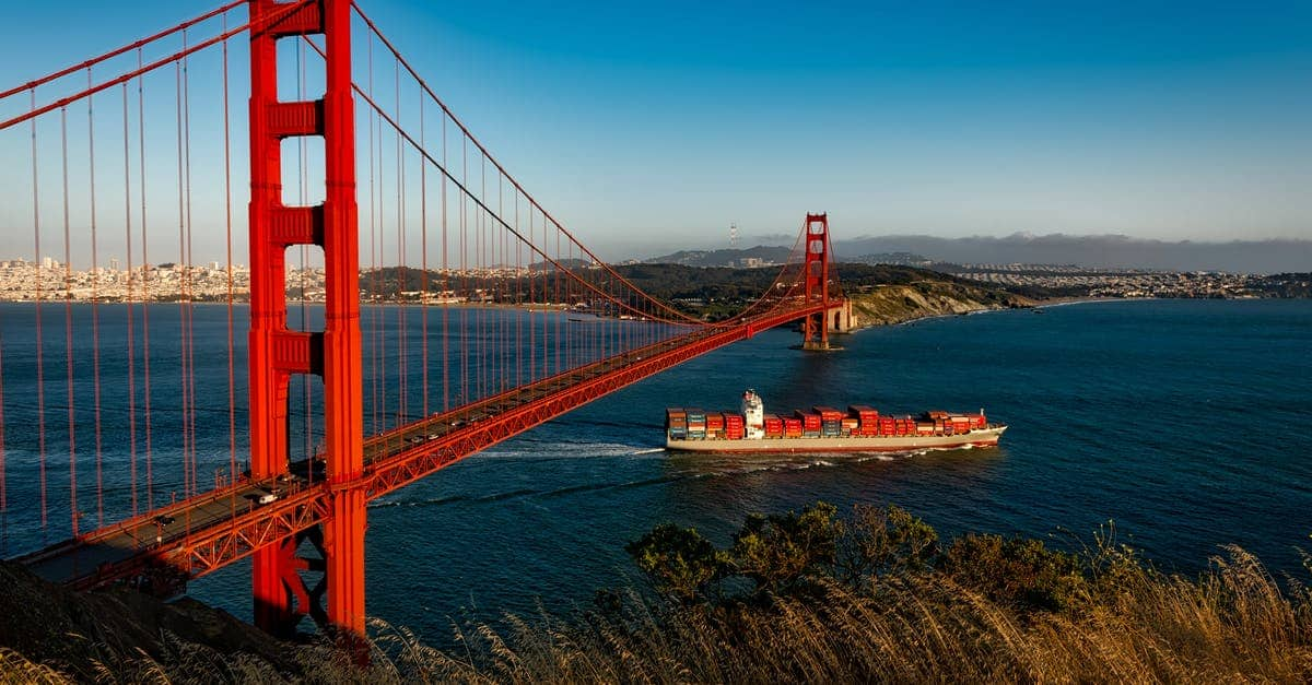 A long bridge over a body of water with Golden Gate Bridge in the background