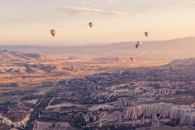 A group of people flying kites in a canyon