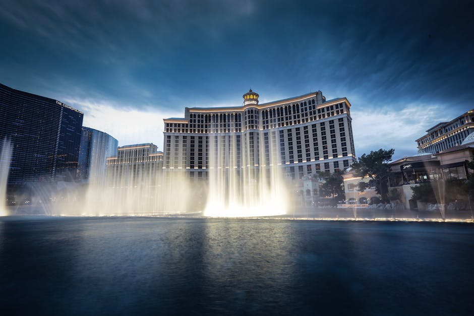 A fountain in a body of water with Bellagio in the background